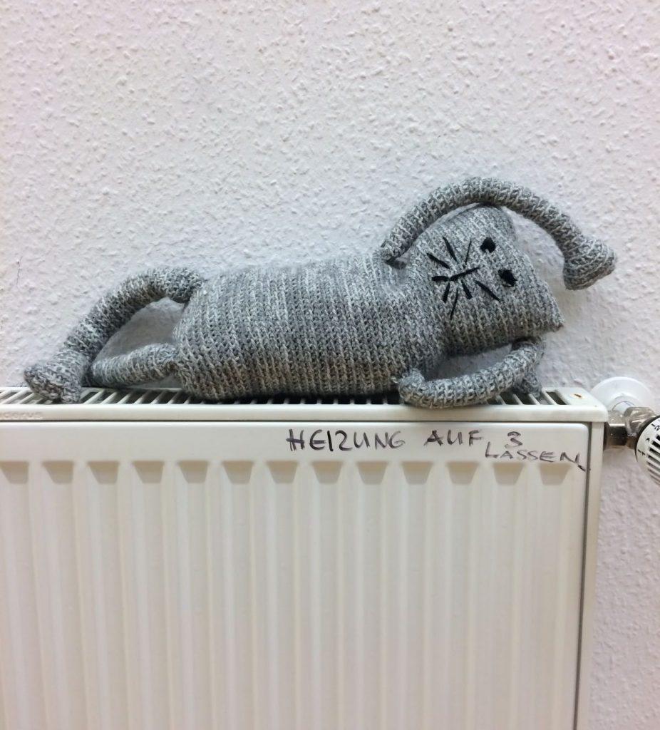 Die Katze auf der warmen Heizung
